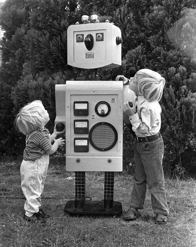 London, England, 29th August 1973, Two little boys study a five foot robot built by their father Peter Stanley in the garden of their London home