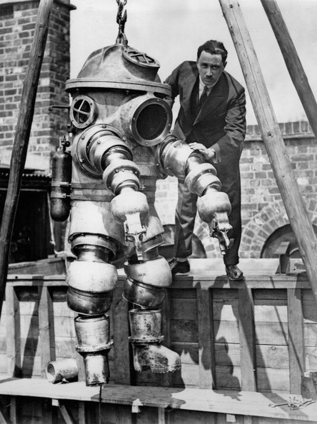 Mr. J.S. Peress, the inventor of the new armoured diving suit, getting his device ready for tests in the tank today at Weybridge. United Kingdom. May 28, 1930.
